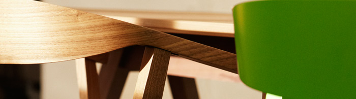 Close-up of two STOCKHOLM chairs, one in walnut veneer and one in green, by IKEA