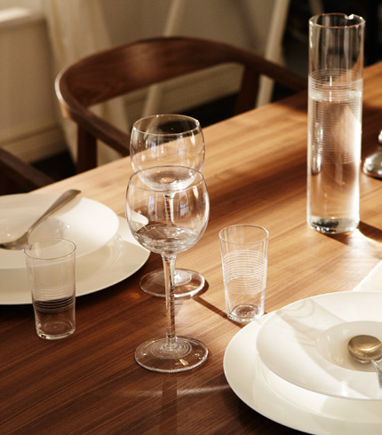STOCKHOLM dining table in walnut set with STOCKHOLM red wine glasses and STOCKHOLM white plates, by IKEA