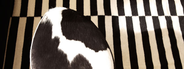 STOCKHOLM pouffe in white and black cowhide on STOCKHOLM flatwoven rug in black and off white, by IKEA