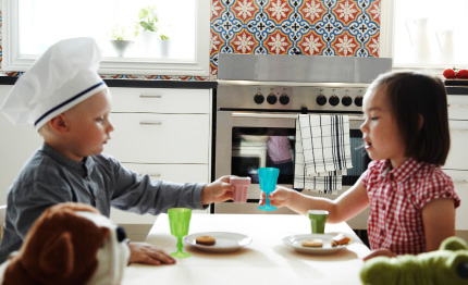 Children playing with toy tableware in a kitchen