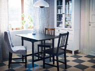 White glass-door cabinet with black-brown drop-leat table and chairs