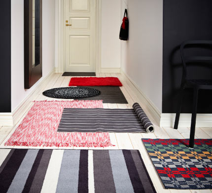 Several small rugs layered in a long hallway