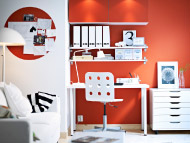 White desk, swivel chair, drawer unit on castors and wall shelves