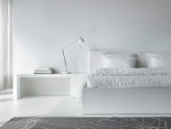 White bedroom with bed, bedside table, textiles and table lamp