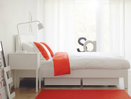 White bedroom with bed, bedside table and red/white bedlinen