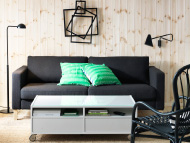 Black three-seat sofa, lighting and white coffee table on castors