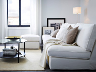 White three-seat sofa, footstool and black-brown coffee table with glass top
