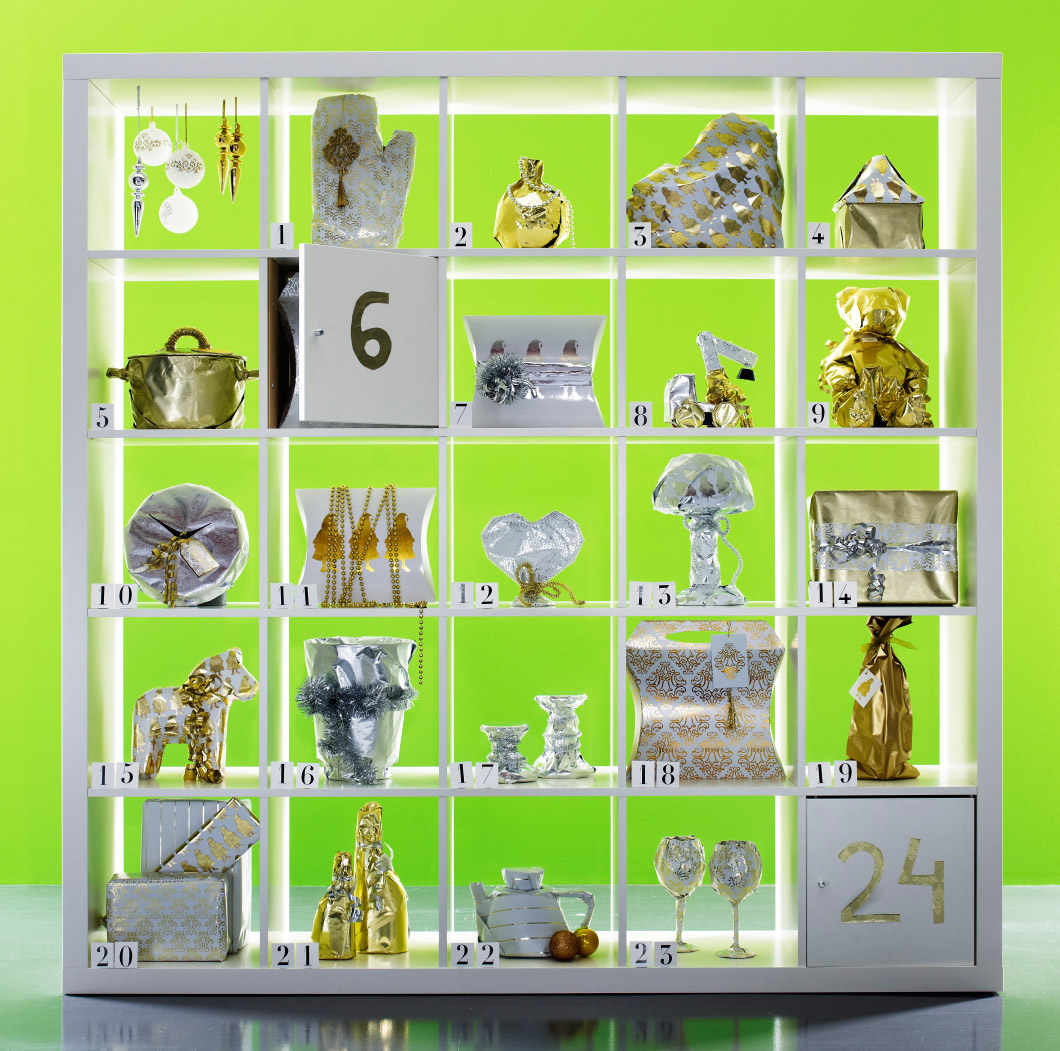 White shelving unit with 24 compartments used as an Advent calendar filled with presents