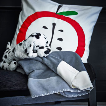 White cushion cover with apple print, dalmatian soft toy and a grey throw