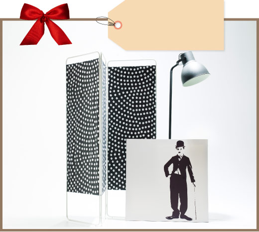 Room divider with black/white dotted fabric, black floor lamp and a picture of Charlie Chaplin
