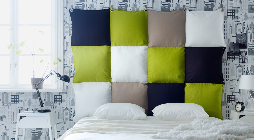 Headboard made of cushions in blue, green, beige and white that has been sewn together