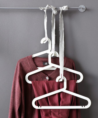 Plastic clothes-hangers fastened to fabric strips and tied to a rail