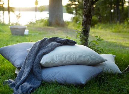A pile of grey cushions and a throw on the grass