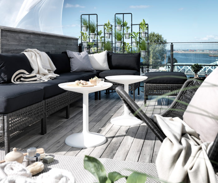 A balcony with outdoor furniture in black-brown woven plastic rattan with black seat/back cushions