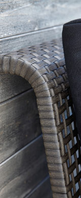 Close-up of the back of the one-seat section in black-brown woven plastic rattan