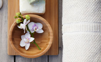 A bamboo bowl with orchids and a white cotton towel