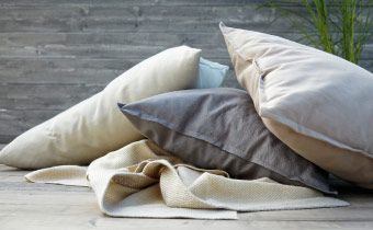 A pile of beige and grey cushions and throws