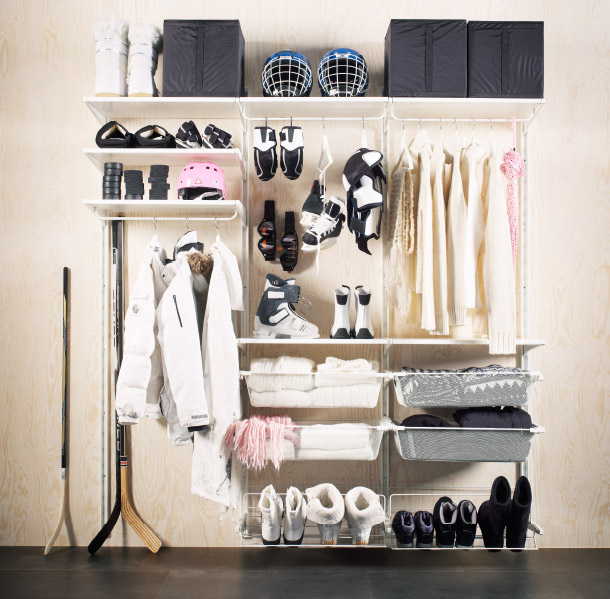 Wall storage solution with shelves and baskets holding winter clothes and accessories