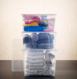 Clothes in transparent plastic storage boxes