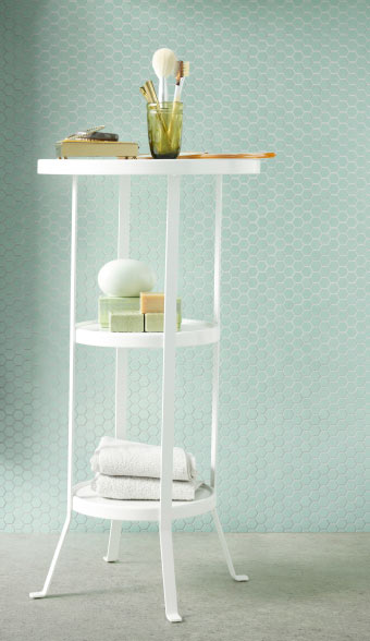 A white pedestal table with towels, soaps and a glass with makeup brushes
