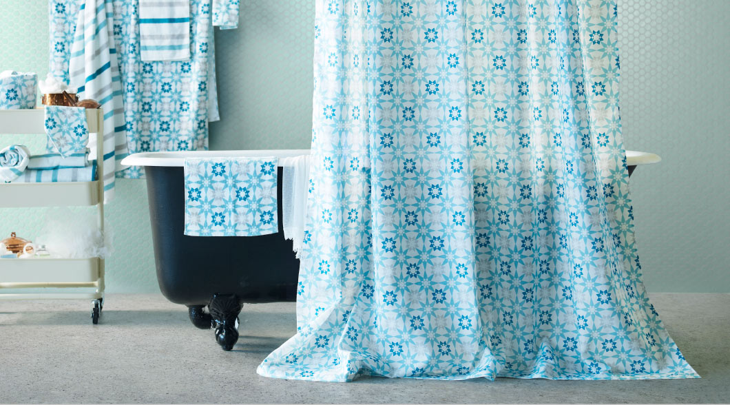 Display of towels in different sizes with stripes and star pattern in turquoise/grey/white and a shower curtain