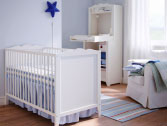 A white baby cot with matching changing table