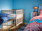 A solid beech baby cot in the parents bedroom