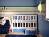 A nursery with a white baby cot with two blue floor drawers