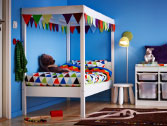 A white bed with canopy and quilt cover set with a triangular pattern in bright colours