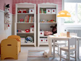 A children's room with two white shelf units with storage boxes in different sizes