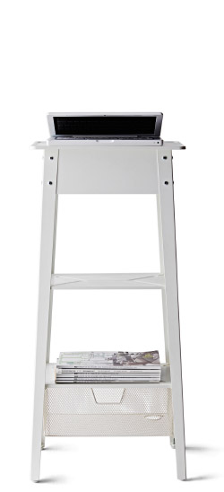 cutout image of the IKEA PS 2014  Standing laptop stand with magazines on the bottom shelf and an open laptop on top.