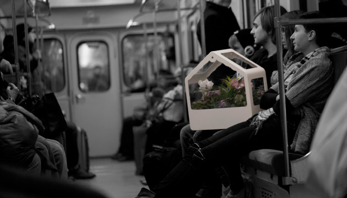 Image of a girl carrying the IKEA PS 2014 greenhouse on train.