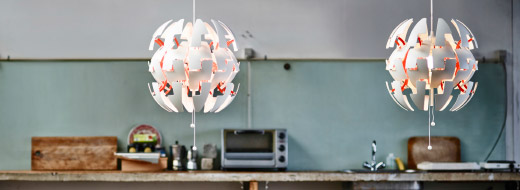 Expandable and contractible pendant lamp show in its expanded form hanging over a dinning room table