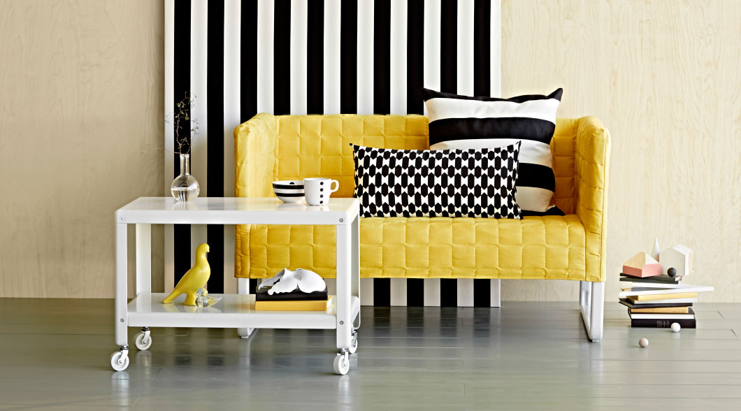 Display of a yellow two-seat sofa and a white coffee table on castors