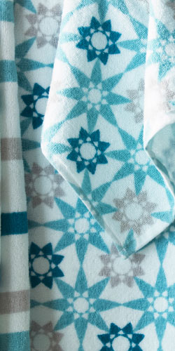 Close-up of towels in different sizes with stripes and star pattern in turquoise, grey and white