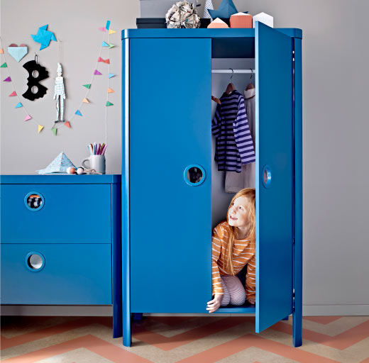 A children´s room with a blue wardrobe and a chest of drawers