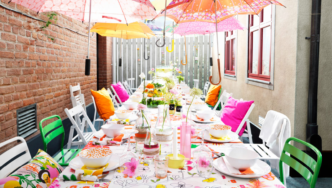 Table in a sunny courtyard, set with bright textiles, flowers and dinnerware. There are colourful umbrellas hanging above.