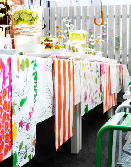 Different types of colourful textiles laid out on a table making a bright tablecloth.