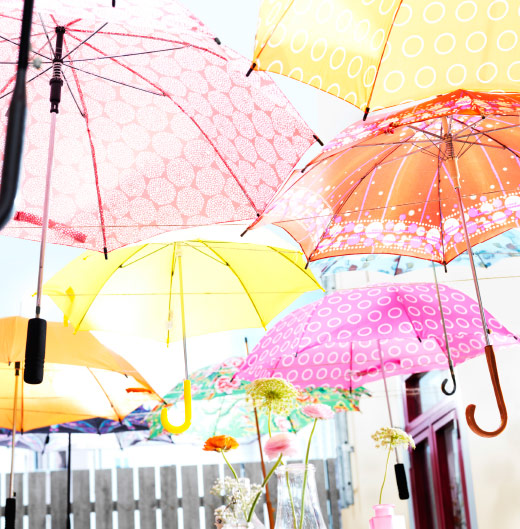Colourful umbrellas hung over table with sunshine shining through.