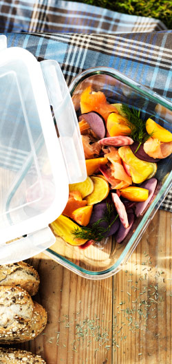 A clear glass tray with lid filled with colourful roasted vegetables.