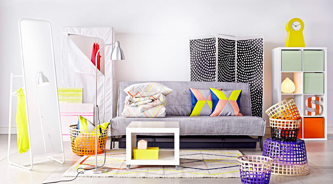 A grey sofa with some colourful cushions and a bright room divider in a living room setting, next to the sofa a full length mirror with a colourful basket.