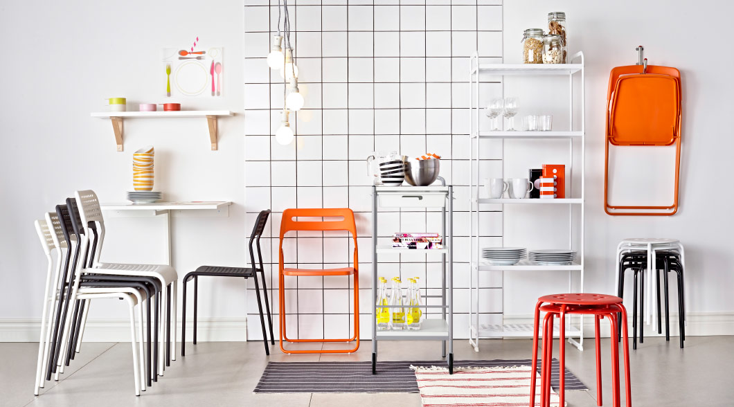 Bright foldable furniture stacked and placed in front of a white tiled wall with a stainless trolley and white table