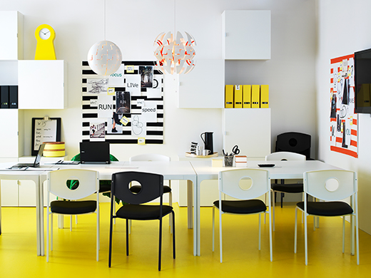 A colourful office space with a yellow floor, white wall cabinets and three BEKANT desks put together to make a conference table.