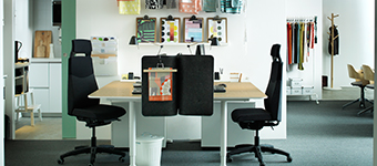 Two BEKANT tables with dark grey screen dividers stand in the centre of a white office with textiles displayed on the walls behind them.