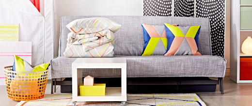 A grey sofa with some colourful cushions and a bright room divider in a living room setting.