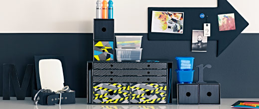 A desktop setting featuring black desk organisers, colourful pens and wall organisation in front of a black and white wall.