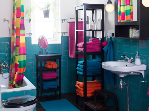 A sunlit bathroom scene with colourful towels on wooden shelving units and a multi-coloured shower curtain