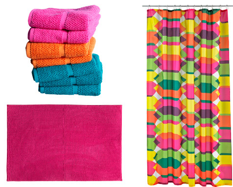 Stack of assorted coloured towels, bathroom rug and a hanging multi-coloured shower curtain