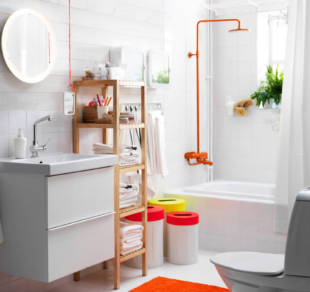 Bright, white bathroom accented with coloured waste bins and an orange
