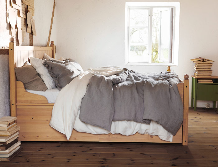 Sunlit bedroom view with solid pine bed frame on wooden floors and a bedside table